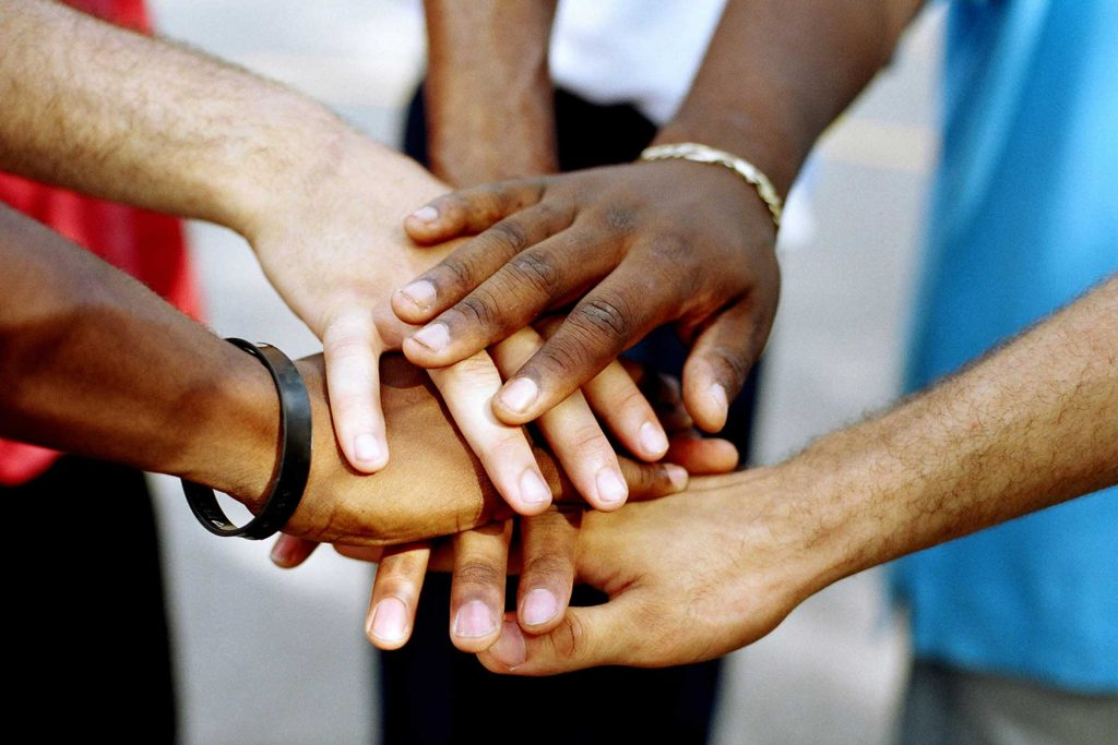 Hands of every difference race all together in a little huddle