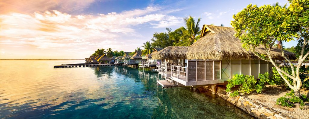 Sunset view of tropical themed vacation houses on waterfront