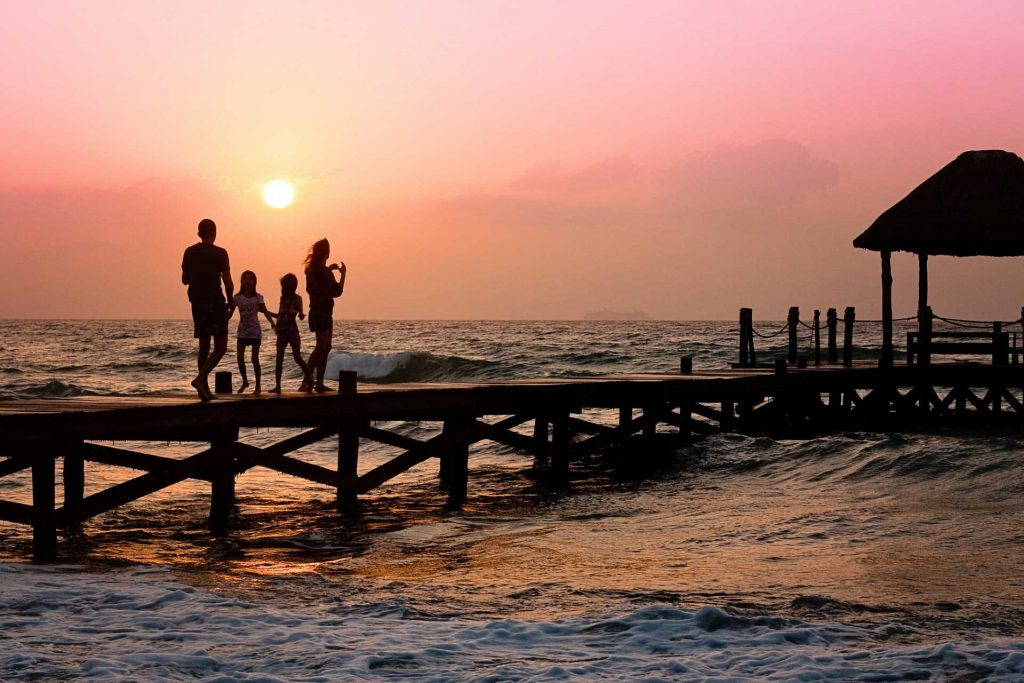 Family walking on pier during sunset
